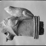 Der bronzene Wasserspeier in Form eine Löwenkopfes, auf  dem sich ein Frosch niedergelassen hat, wurde in einem archaische Wasserbecken im Heraion von Samos gefunden. Er befindet sich heute im Athener Nationalmuseum.